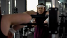 Obese male exhausted after workouts in gym, looking at his reflection in mirror royalty free stock photos