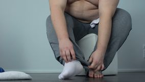 Obese male hardly putting socks, lack of physical activity, sedentary lifestyle stock footage
