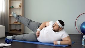 Obese male lifting leg lying on mat, healthy lifestyle, sport leisure, exercises stock photos