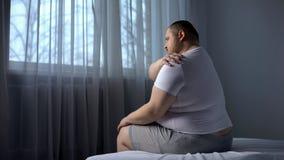 Obese male massaging shoulder muscles, orthopedic and rheumatologic disorders. Stock photo royalty free stock photos