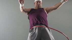 Obese male trying to twist hula hoop, dreams of healthy and fit body, weightloss. Stock footage stock footage