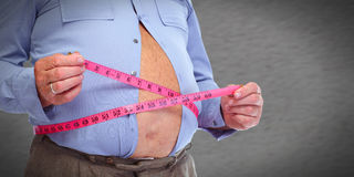 Obese man abdomen with measuring tape. Royalty Free Stock Image