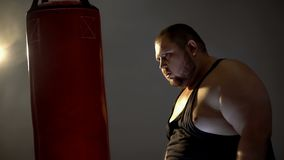 Obese man with aggression looking at punching bag imaging his opponent, box royalty free stock images