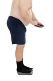 Obese man calculates calories on scales. Fat man calculates calories standing on a weight scales Stock Photography