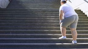 Obese man climbing stairs, overweight causes pain in joints, varicose veins