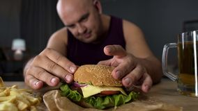 Obese man cooking big burger, overeating gourmet admiring his meal, close-up royalty free stock photography