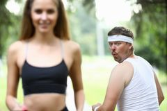 Obese man doing morning jogging in park. Obese men doing morning jogging in park. A girl with great figure runs by. The guy turns around look and surprisingly royalty free stock photography