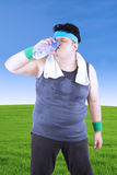 Obese man is drinking in the meadow Royalty Free Stock Image