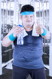 Obese man drinks water at gym Royalty Free Stock Images