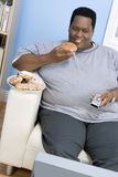 Obese Man Eating Donut. An African American man eating donut while watching television Royalty Free Stock Images