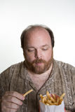 Obese man eating fast food Royalty Free Stock Image