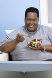 Obese Man Eating Fruits Royalty Free Stock Image