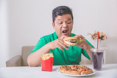 Obese man eating junk food. Obese man having his lunch of junk or unhealthy food at home Stock Photos