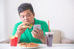Obese man eating junk food. Obese man having his lunch of junk or unhealthy food at home while using mobile phone Royalty Free Stock Photos