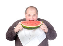 Obese man eating watermelon. Obese man with a serviette bib around his neck standing eating a large slice of fresh juicy watermelon isolated on white Royalty Free Stock Images