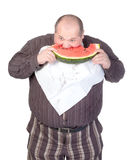 Obese man eating watermelon. Obese man with a serviette bib around his neck standing eating a large slice of fresh juicy watermelon isolated on white Royalty Free Stock Photography
