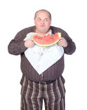 Obese man eating watermelon. Obese man with a serviette bib around his neck standing eating a large slice of fresh juicy watermelon isolated on white Royalty Free Stock Photos