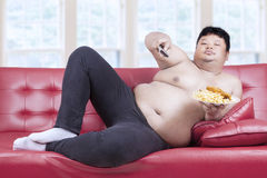 Obese man eats fast food 1. Fat man eats fast food while watching tv at home Stock Photography