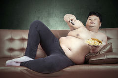 Obese man eats fast food. Fat man eats fast food while watching tv at home Royalty Free Stock Photography