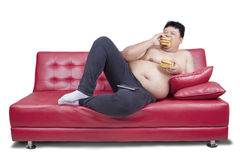 Obese man eats two hamburger on sofa. Portrait of a young obese man leans on the couch while eating two hamburger, isolated on white background Royalty Free Stock Images