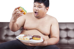 Obese man enjoying donuts. Picture of a young obese man sitting on brown sofa and enjoy donuts, isolated on white background Royalty Free Stock Photography