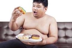 Obese man enjoying donuts Royalty Free Stock Photography