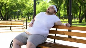 Obese man feels side aches after intense workouts outdoors, health problems. Stock photo stock image