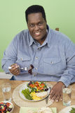 An Obese Man Having Food. Portrait of a happy obese man having healthy food at home Stock Image