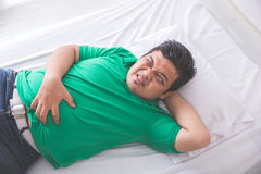 Obese man having stomach ache while laying on a bed Royalty Free Stock Photography