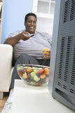 Obese Man Holding Glass Of Juice. Happy African obese man watching television while holding glass of juice Stock Image