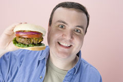 Obese Man Holding Hamburger Stock Photo
