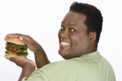 An Obese Man Holding Hamburger. Portrait of an obese African American men holding hamburger isolated over white background Royalty Free Stock Images