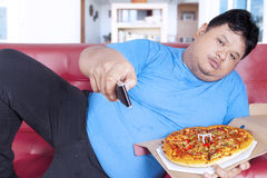 Obese man holds pizza and remote 1 stock images