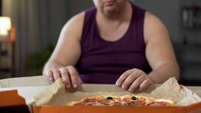 Obese man looking at fatty pizza on table, junk food addiction, overeating stock photos