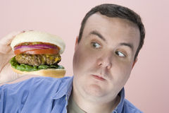 Obese Man Looking At Hamburger Royalty Free Stock Photography
