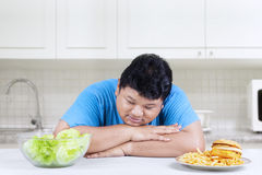 Obese man looking at salad 1 Royalty Free Stock Images