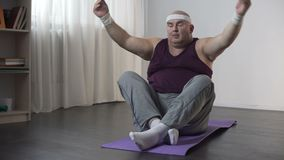 Obese man meditating on mat and falling down, funny chubby male doing yoga stock video footage