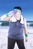 Obese man with mineral water on the bottle Stock Photos