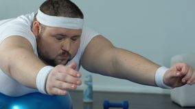Obese man relaxing fitness ball after home workout complex, power and endurance. Stock footage stock footage