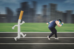 Obese man running away from a cigarette Royalty Free Stock Image