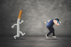 Obese man running with a cigarette Stock Images