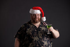 Obese man in Santa Hat. An obese man in Santa hat and tropical shirt Royalty Free Stock Image