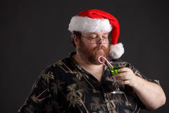 Obese man in Santa Hat. An obese man in Santa hat and tropical shirt Royalty Free Stock Photos