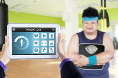 Obese man with scale and app of weight loss. Overweight person holding a scale at gym with weight loss applications on the digital tablet screen Stock Photography