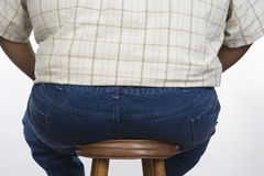 An Obese Man Sitting On A Stool. Rear view of an obese men sitting on a stool isolated over white background Stock Photos