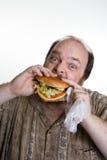 Obese man som äter snabbmat Royaltyfria Foton