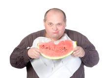 Obese man som äter vattenmelonen Arkivfoto