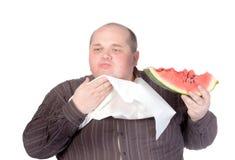 Obese man som äter vattenmelonen Royaltyfri Bild