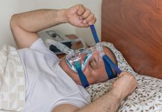 Obese man suffering from sleep apnea. Man wearing a mask for treating sleep apnea. Mildly obese man suffering from sleep apnea and having a CPAP treatment royalty free stock photos
