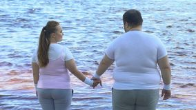Obese man taking girlfriends hand, couple enjoying beautiful view of river